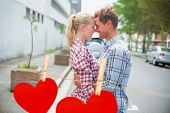 Couple in check shirts and denim hugging each other against hearts hanging on a line