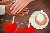 Couple holding hands beside cappuccino against hearts hanging on a line