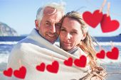 Smiling couple wrapped up in blanket on the beach against hearts hanging on a line
