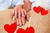 Hearts hanging on a line against retired couple holding hands