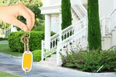 Key in hand on house background, Real estate concept
