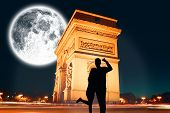 Attractive couple smiling and cheering against large moon over arc de triomph
