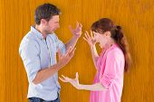 Couple arguing with each other against wooden pine table