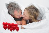 Loving middle aged couple under the duvet against love hearts
