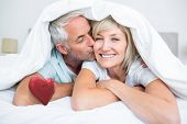 Closeup of mature man kissing womans cheek in bed against red heart