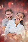 Cute couple hugging and smiling at camera against light design shimmering on red