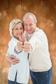 Happy mature couple showing thumbs up against light design shimmering on green