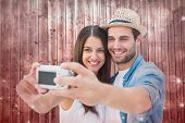 Happy hipster couple taking a selfie against shimmering light design on red