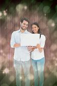 Attractive young couple holding their laptop against light design shimmering on green