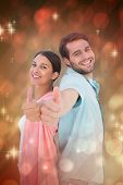 Happy couple showing thumbs up against light design shimmering on red