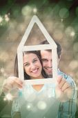 Happy young couple with house shape against light design shimmering on green