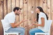 Couple sitting on chairs arguing against wooden planks