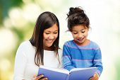 family, children, education and happy people concept - happy mother and little daughter reading book over green background