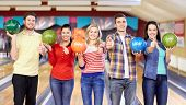 people, leisure, sport, friendship and entertainment concept - happy friends holding balls and showing thumbs up in bowling club