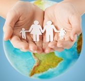 people, population, charity and life concept - close up of human hands holding paper family over earth globe and blue background