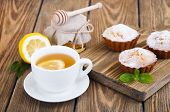 picture of bakeshop  - A cup of tea with lemon and honey homemade muffins on wooden background