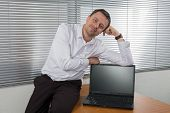 Businessman Sitting At Desk In Bright Office