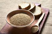 pic of sesame seed  - Sesame seeds in bowl and wooden spoon with wholegrain bread in the back photographed with natural light  - JPG