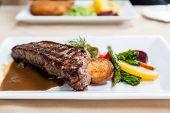 stock photo of marsala  - Grilled juicy New York strip loin beef steak served with potatoes fresh vegetables and marsala portobello mushroom sauce - JPG