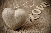 a cardboard heart and wooden letters forming the word love on a rustic wooden surface, in sepia toning