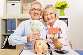 Happy senior couple with Euro money bills and house and piggy bank