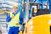 stock photo of manufacturing  - Forklift driver standing proud in manufacturing plant - JPG