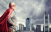 Senior superhero standing in front of a dark city