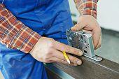 Close-up carpenter hands with doorlock during lock process installation into wood door