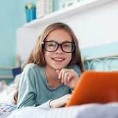8 years old child having fun using laptop at her bedroom, square photo