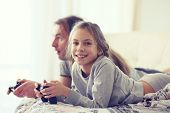 Child playing video game on tv with father in morning at bed at home