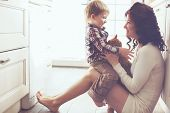 pic of petting  - Mother with her baby playing with pet on the floor at the kitchen at home - JPG
