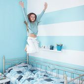 8 years old kid girl jumping on the bed at her room, square photo