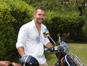 Happy casual stubbly caucasian man with scooter and helmet in garden, looking at camera.