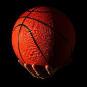 Male hands holding basketball ball on dark background