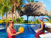 stock photo of pool ball  - mother and son playing ball at the pool on tropical beach - JPG