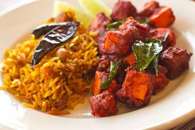 stock photo of crispy rice  - Crispy spicy Kadai Paneer Tofu with tamarind rice and lime wedges - JPG