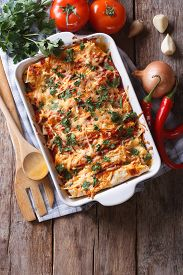 pic of enchiladas  - Mexican enchilada in a baking dish with the ingredients on the table - JPG