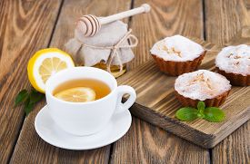 picture of bakeshop  - A cup of tea with lemon and honey homemade muffins on wooden background  - JPG