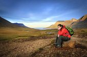 picture of fjord  - Woman is taking a rest from a hike in the Seydisfjordur fjord valley in Iceland - JPG