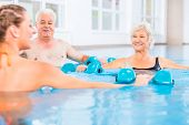 image of gymnastics  - People young and senior in water gymnastics physiotherapy with dumbbells - JPG