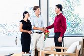 stock photo of southeast asian  - Mixed couple in furniture store with Asian shop assistant shaking hands sealing deal - JPG