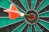 stock photo of bullseye  - Darts board with single arrow in bullseye - JPG