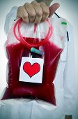 foto of hemostasis  - closeup of a doctor holding a blood bag with a sticker of a red heart - JPG