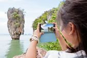 pic of james bond island  - Women tourist he is shooting a beautiful scenic view by mobile phone at Khao Tapu or James Bond Island in Ao Phang Nga Bay National Park Thailand - JPG