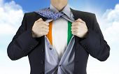 image of ivory  - businessman showing Ivory Coast flag underneath his shirt over blue sky - JPG