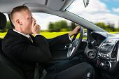 stock photo of yawn  - Portrait Of A Young Businessman Yawning While Driving Car - JPG