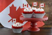 stock photo of flag confederate  - Happy Canada Day celebration cupcakes on red cake stand with red and white maple leaf flag against a rustic distressed wood background - JPG