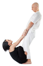foto of thai massage  - Young woman in traditional thai position with legs crossed being stretched by therapist - JPG