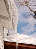 stock photo of soffit  - icicles hanging from the eaves and thick snow on a roof - JPG