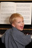 Happy Young Boy And Piano